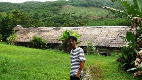 Artist Jainal Amambing outside a longhouse in his native Sabah, Malaysia