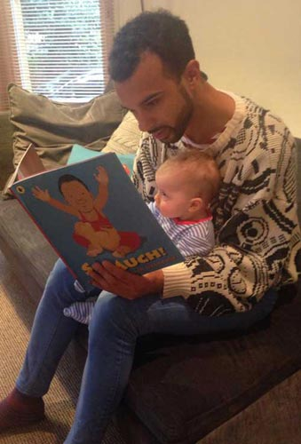 Dad and baby reading So Much! written by Trish Cooke and illustrated by Helen Oxenbury