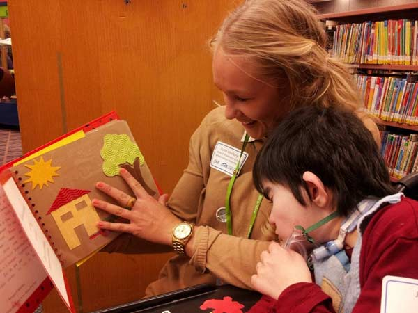 A librarian at the IBBY Collection for Young People with Disabilities at Toronto Public Library shares a tactile book with a disabled child