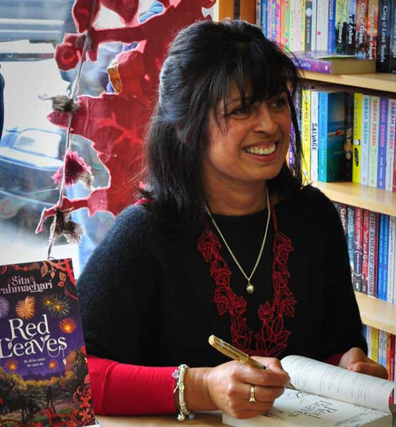 Author Sita Brahmachari at a book-signing event, wearing the artichoke charm given to her by her husband following publication of her first novel Artichoke Hearts