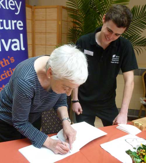 Jessica Souhami signing a book for Ilkley Literature Festival Stage Manager Conor Whelan
